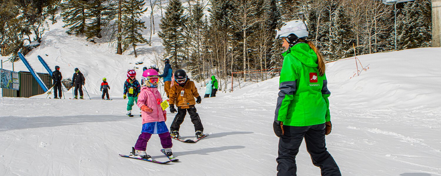 Snowsports Instructor teaching two kids on skis