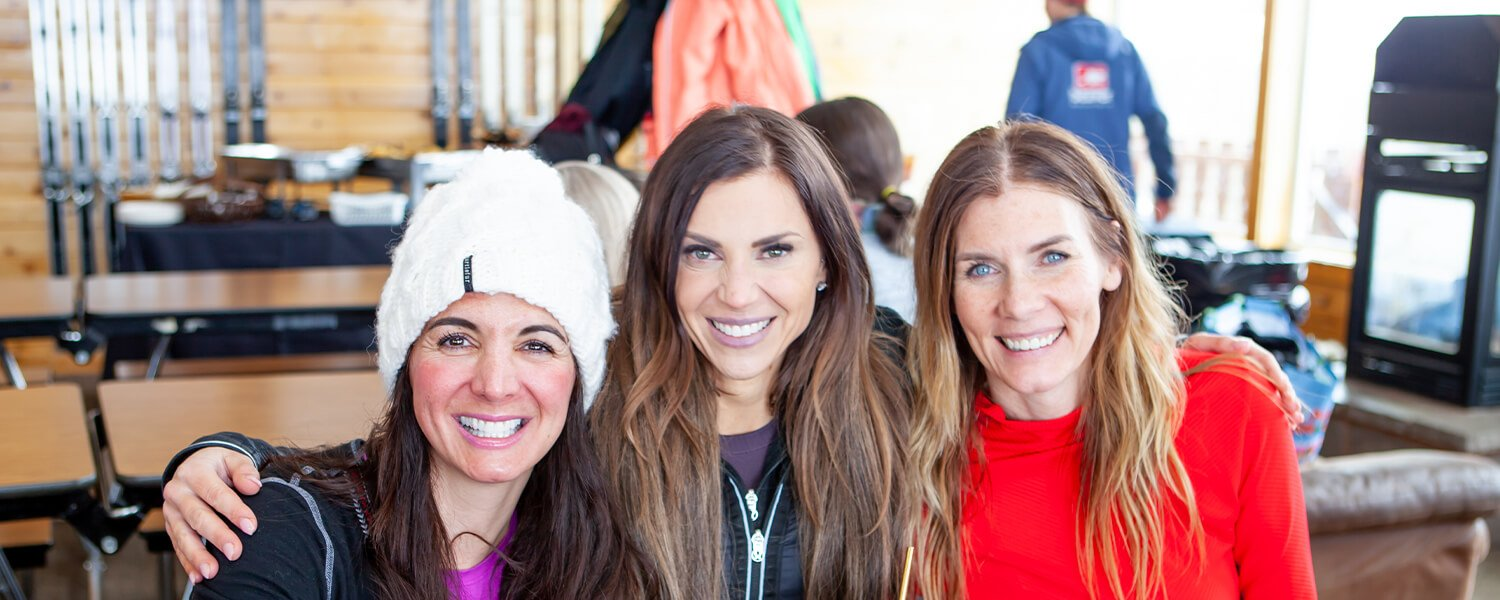 Group of three women smiling in the lodge