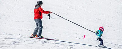 Parent skiing with beginner child