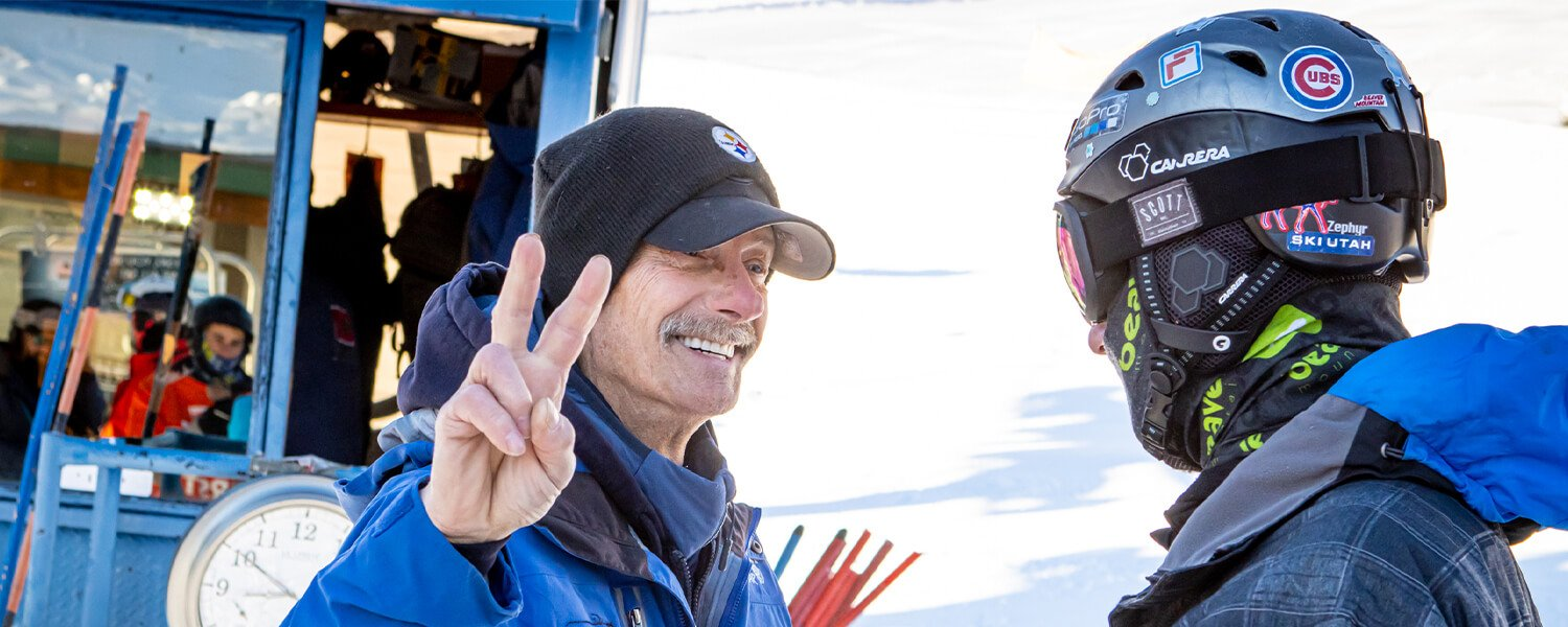 Beaver Mountain Staff members, one in a hat putting up two finger peace symbol