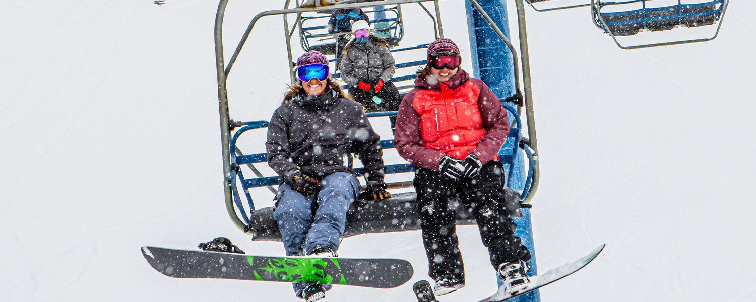 Two snowy chairlift riders
